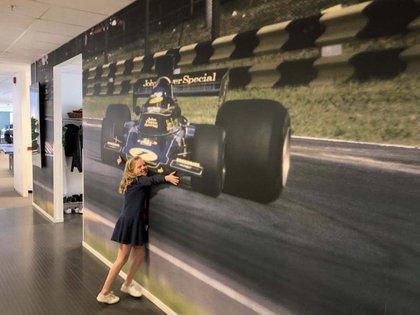 La nieta de Ronnie y Barbro abraza la gigantografía de su abuelo. La imagen es del Lotus 72 en la Horquilla del Autódromo de Buenos Aires en 1973.