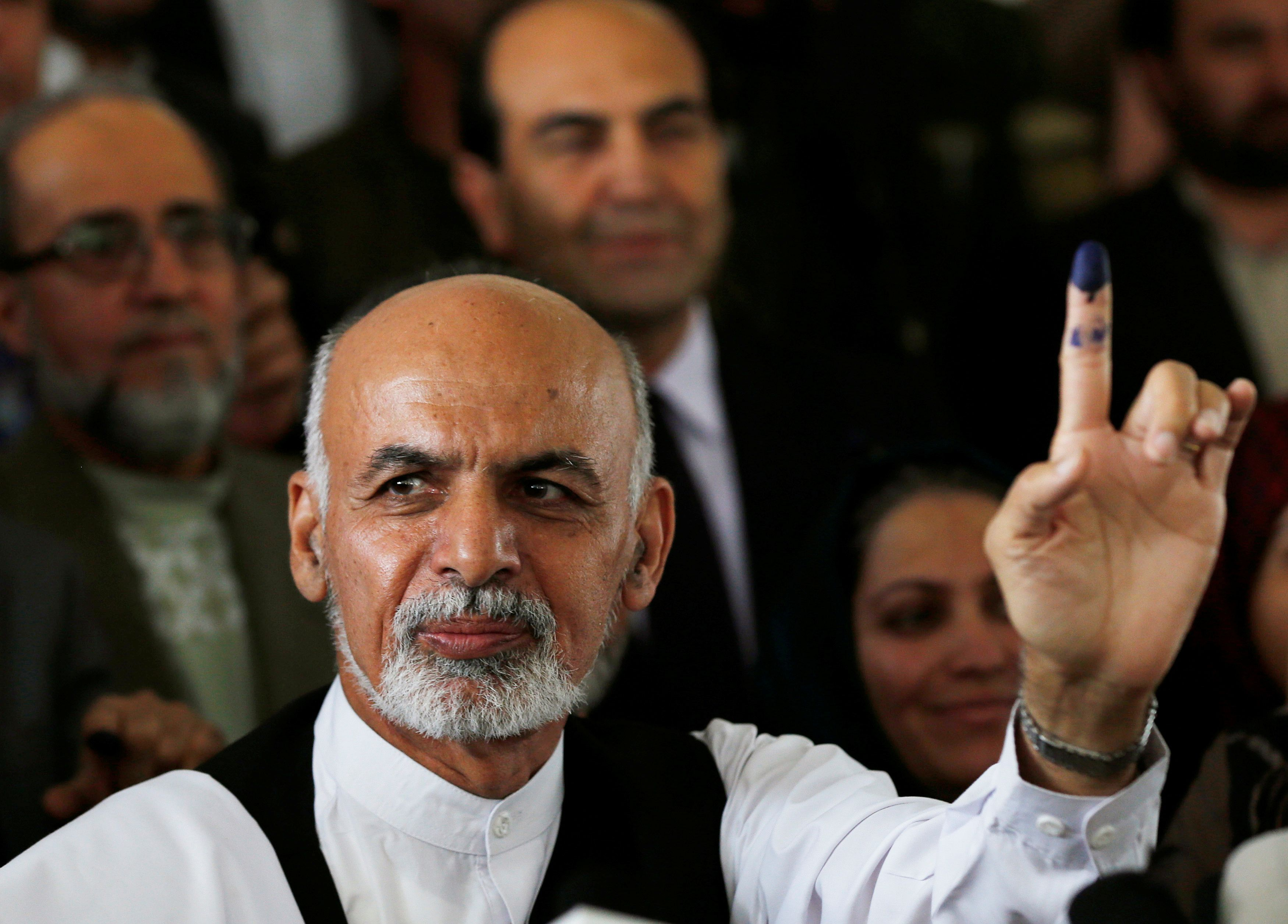 FILE PHOTO: Afghan presidential candidate Ashraf Ghani Ahmadzai holds up his ink-stained finger after voting in the presidential election in Kabul June 14, 2014. Afghans headed back to the polls on Saturday for a second round of voting to elect a successor to President Hamid Karzai in a decisive test of Afghanistan's ambitions to transfer power democratically for the first time in its tumultuous history.  REUTERS/Stringer/File Photo