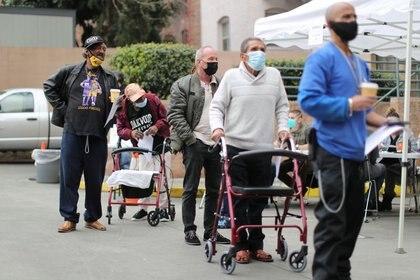 Gente hace fila para recibir la vacuna COVID-19 en el albergue para personas sin hogar LA Mission en Skid Row, en Los Ángeles, California, Estados Unidos. 10 de febrero, 2021. REUTERS/Lucy Nicholson