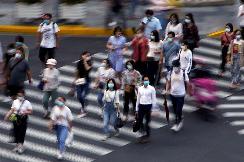FOTO DE ARCHIVO: Varias personas con mascarillas cruzan un paso de cebra en una calle de Shanghái, China, el 16 de julio de 2020. REUTERS/Aly Song