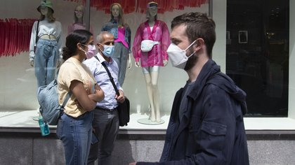 """People wearing protective masks wait in line to enter at a La Maison Simons Inc. store in Montreal, Quebec, Canada, on Monday, May 25, 2020. Premier Francois Legault said in news conference in Quebec City that the province is entering """"a new stage."""""""