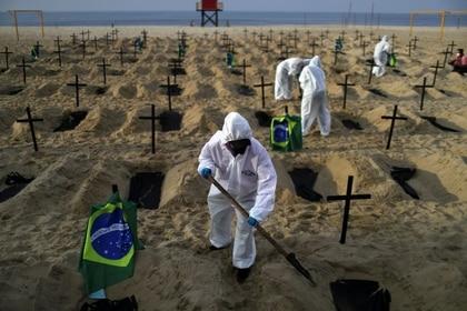 Activistas de la ONG Río de Paz con equipo de protección cavan tumbas en la playa de Copacabana para simbolizar a los muertos por la enfermedad del coronavirus (COVID-19) durante una manifestación en Río de Janeiro, Brasil, 11 junio 2020 (REUTERS/Pilar Olivares)