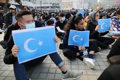 Manifestantes de Hong Kong sostienen banderas uigures del Turquestán Oriental en un acto de apoyo a los derechos humanos de los uigures del Xinjiang en Hong Kong, China, el 22 de diciembre,2019. REUTERS/Lucy Nicholson