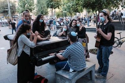 Un grupo de jóvenes usando máscaras se reúnen alrededor de un piano en Jerusalem, Israel. Photo: Nir Alon/ZUMA Wire/dpa