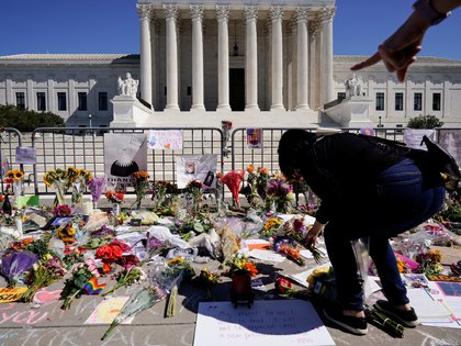 A woman places flowers as people mourn the death of Associate Justice Ruth Bader Ginsburg at the Supreme Court in Washington, U.S., September 20, 2020.      REUTERS/Joshua Roberts