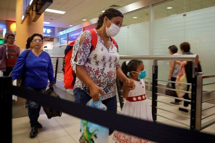 Pasajeros usan mascarillas protectoras debido al brote de coronavirus en el país, en el Aeropuerto Internacional Jorge Chávez en Lima, Perú. 6 de marzo de 2020. REUTERS/Sebastián Castañeda.