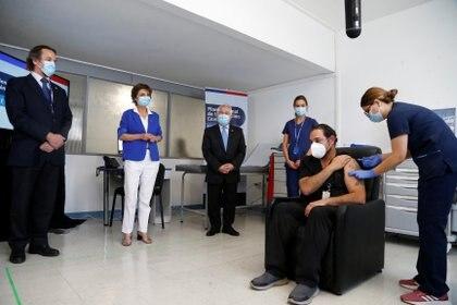 El Dr. Juan Emilio Cornejo recibe una inyección con una dosis de la vacuna COVID-19 de Pfizer-BioNtech mientras el Ministro de Salud de Chile, Enrique Paris, observa en el Hospital Metropolitano, mientras continúa el brote de la enfermedad coronavirus (COVID-19), en Santiago de Chile el 24 de diciembre