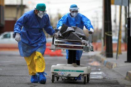 Personal de la salud conduce al Servicio Médico Forense, el cuerpo de una persona fallecida por COVID-19, en la fronteriza Ciudad Juárez, en el estado de Chihuahua (Foto: EFE/Luis Torres)