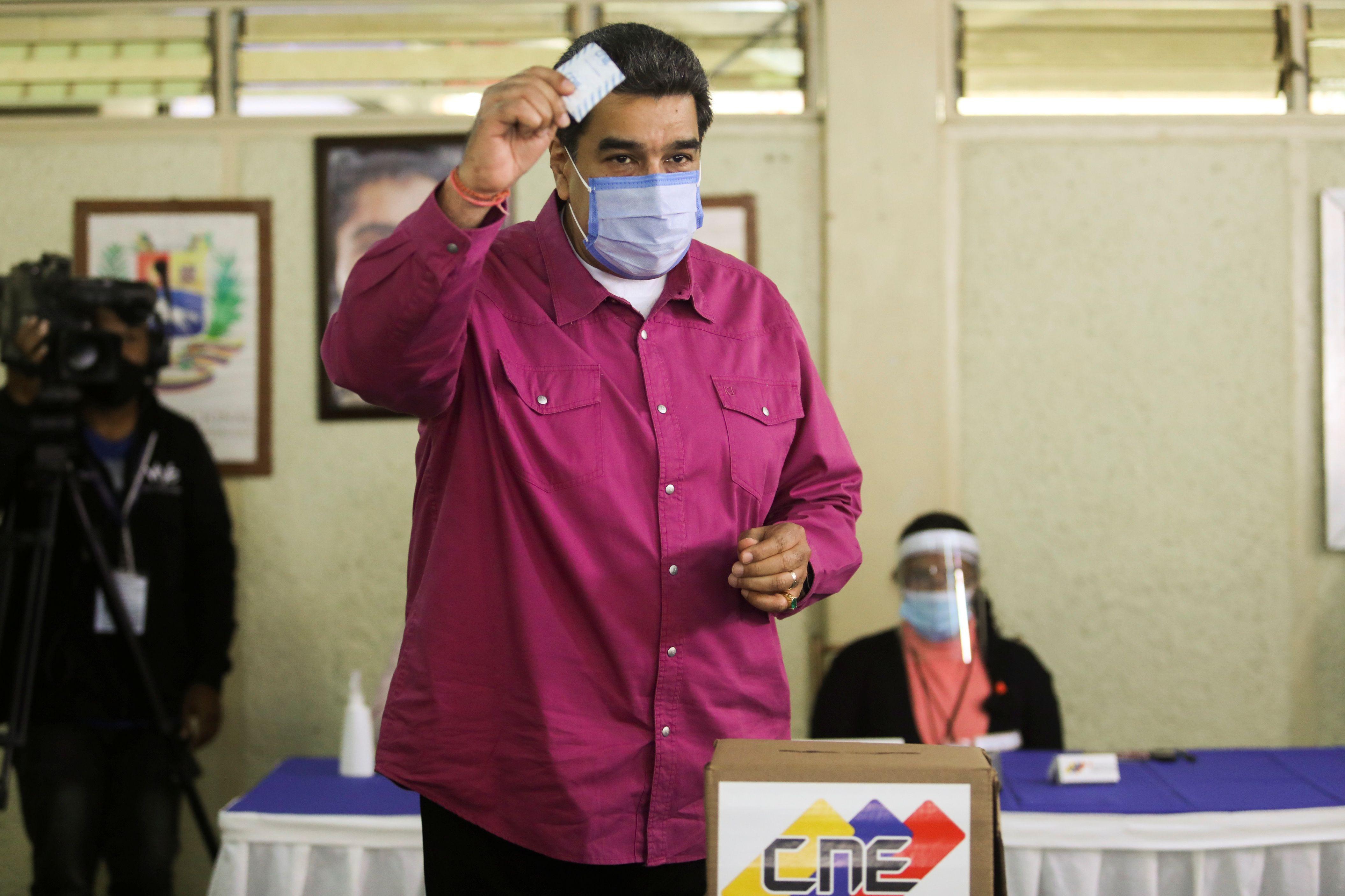 El dictador de Venezuela, Nicolás Maduro, muestra su boleta mientras vota en un colegio electoral durante las elecciones parlamentarias en Caracas, Venezuela, 6 de diciembre de 2020. REUTERS/Fausto Torrealba