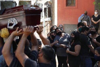 En esta fotografía de archivo del 22 de septiembre de 2020, familiares de Tranquilino Ruiz Cabrera, quien trabajaba como taxista y murió por complicaciones relacionadas con el COVID-19, lloran durante su entierro en el cementerio de Recoleta de Asunción, en Paraguay. (Foto AP / Jorge Saenz, Archivo)