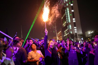 Una mujer sostiene una bengala mientras otras miran poco antes de celebrar el año nuevo en Plaza Italia durante una protesta contra el gobierno de Chile en Santiago, Chile, el 31 de diciembre de 2019. (REUTERS / Pablo Sanhueza)