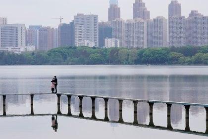Una pareja con mascarillas de protección se abraza sobre un lago en Wuhan (Reuters)