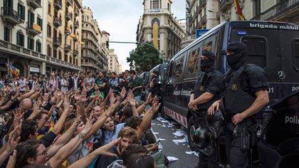 Las personas protestan la violencia de las fuerzas policiales durante el reférendum celebrado el domingo. En la foto los Mossos d'Esquadra se interponen con la sede de la Policía Nacional en Barcelona (Getty)