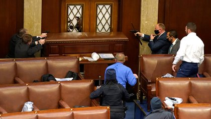 Oficiales de policía del Capitolio de EEUU apuntan sus armas a un manifestante detrás de una puerta que fue vandalizada en la Cámara de Representantes el 06 de enero de 2021 en Washington, DC (Drew Angerer/Getty Images/AFP)