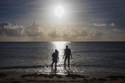 ARCHIVO-- Una pareja se adentra en el Océano Atlántico en Miami Beach, Florida, el 1 de septiembre de 2019. Los océanos de la Tierra están bajo una fuerte presión por el cambio climático, advierte un importante nuevo informe de las Naciones Unidas emitido el 25 de septiembre que amenaza todo desde la capacidad cosechar mariscos para el bienestar de cientos de millones de personas que viven a lo largo de las costas. (Scott McIntyre / The New York Times)