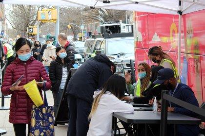 Funcionarios del Departamento de Salud de Nueva York comprueban los datos de las personas que esperan para vacunarse contra la covid-19 en los autobuses convertidos en unidad móvil para inmunización, estacionados en Sunset Park, Brooklyn, Nueva York (EE.UU). EFE/Jorge Fuentelsaz/Archivo