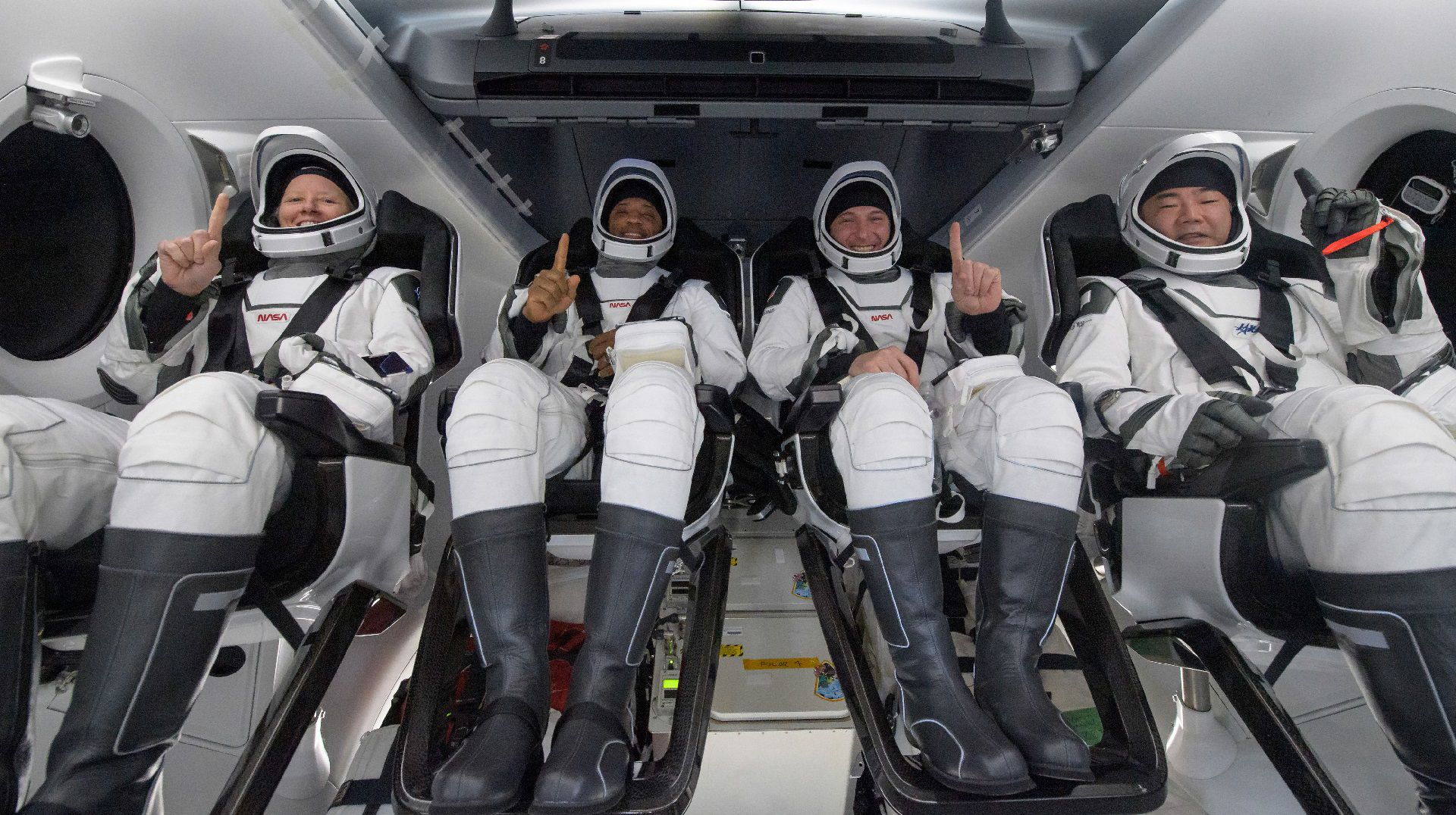 """This handout image courtesy of NASA and made available on May 2, 2021, shows NASA astronauts from left:- Shannon Walker, Victor Glover, Mike Hopkins, and Japan Aerospace Exploration Agency (JAXA) astronaut Soichi Noguchi, strapped in their seats inside the SpaceX Crew Dragon Resilience spacecraft onboard the SpaceX GO Navigator recovery ship shortly after having landed in the Gulf of Mexico off the coast of Panama City, Florida, on May 2, 2021. - NASA�s SpaceX Crew-1 mission was the first crew rotation flight of the SpaceX Crew Dragon spacecraft and Falcon 9 rocket with astronauts to the International Space Station as part of the agency�s Commercial Crew Program. (Photo by Bill INGALLS / (NASA/Bill Ingalls) / AFP) / RESTRICTED TO EDITORIAL USE - MANDATORY CREDIT """"AFP PHOTO /NASA/Bill INGALLS"""" - NO MARKETING - NO ADVERTISING CAMPAIGNS - DISTRIBUTED AS A SERVICE TO CLIENTS"""