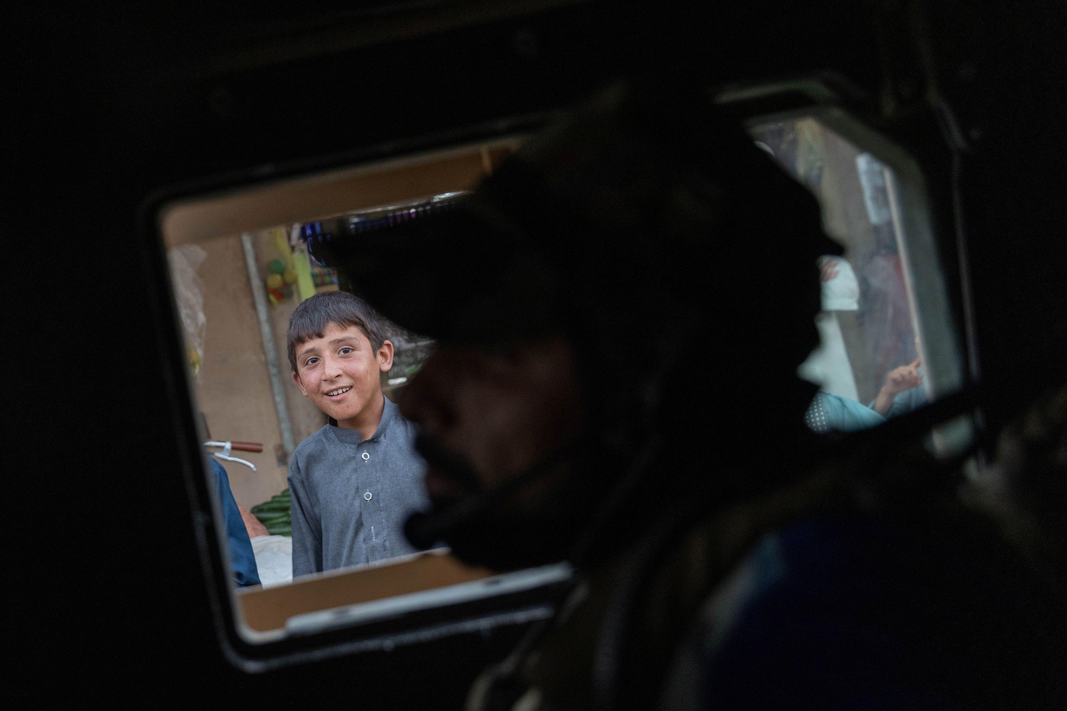 Un niño observa cómo el convoy de las fuerzas especiales afganas pasa por un mercado durante una misión de combate contra los talibanes, en la provincia de Kandahar, Afganistán, el 12 de julio de 2021. Foto tomada el 12 de julio de 2021.
