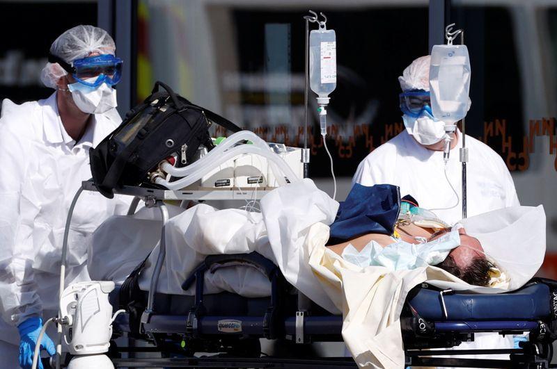 Un equipo de rescate francés con trajes protectores lleva a un paciente al hospital de la Universidad de Estrasburgo. 16 de marzo de 2020. REUTERS/Christian Hartmann