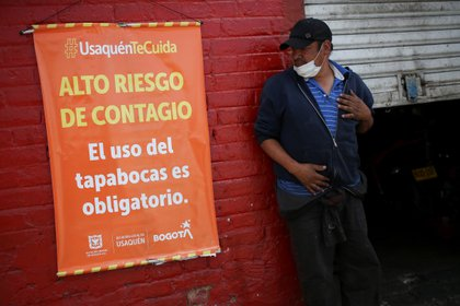 """A man wearing a face mask under his chin looks at a sign that reads """"High risk of contagion, the use of face masks is mandatory"""" in one of the neighbourhoods where the mayor's office decreed strict quarantine, amidst an outbreak of the coronavirus disease (COVID-19), in Bogota, Colombia January 5, 2021. REUTERS/Luisa Gonzalez"""