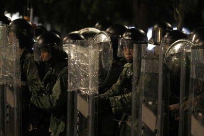 Policías antimotines colocados tras sus escudos ante manifestantes en el distrito de Yuen Long, en Hong Kong, el sábado 27 de julio de 2019. (AP Foto/Bobby Yip)