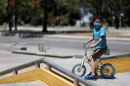 Un niño juega en un parque durante un permiso de 8 horas para que los menores de 14 años salgan al exterior, mientras continúa la cuarentena nacional debido al brote de coronavirus en Caracas, Venezuela, el 26 de abril de 2020 (REUTERS/Manaure Quintero)