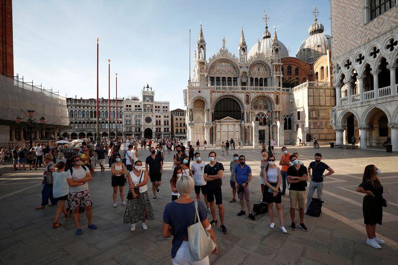 Turistas con mascarillas escuchando a un guía en una visita a la Plaza de San Marcos en Venecia. Sep 11, 2020. REUTERS/Guglielmo Mangiapane