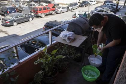 Alex González limpia sus equipos antes de entrar a su departamento en Tijuana donde vive con su mamá y hermano.