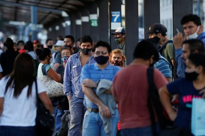 People wearing faces mask as a protection against the coronavirus disease (COVID-19) wait for the bus, in Buenos Aires, Argentina March 31, 2021. REUTERS/Agustin Marcarian