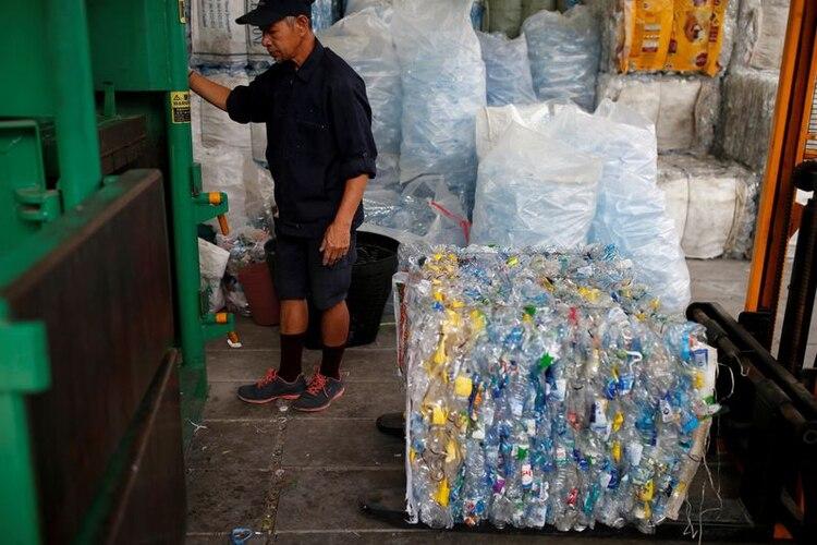 Un hombre comprimiendo plástico reciclado con el que se fabricará fibra para tela en un monasterio en Bangkok (REUTERS/Soe Zeya Tun)