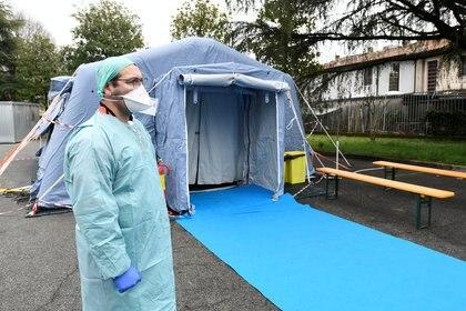 Un trabajador médico con máscara protectora espera en un puesto de control médico a la entrada del hospital Spedali Civili de Brescia, Italia, el 3 de marzo de 2020 (REUTERS/Flavio Lo Scalzo)