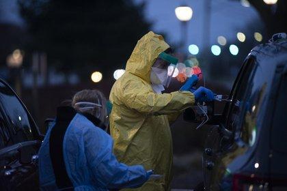 Un trabajador del sector salud realiza una prueba de coronavirus con un cotonete nasal en un punto de pruebas para personas en sus autos en la unidad de urgencias de ProHEALTH de Jericho en Nueva York, el 18 de marzo de 2020. (Johnny Milano/The New York Times)