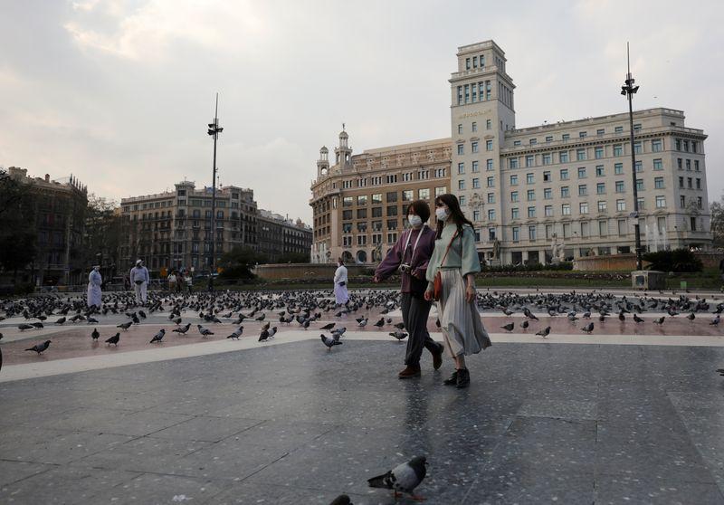 Mujeres usando mascarillas mientras caminan por una vacía Plaça de Catalunya, en medio de las preocupaciones por la pandemia del coronavirus, en Barcelona, España. REUTERS/Nacho Doce/Archivo