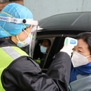FILE PHOTO: A security officer in a protective mask checks the temperature of a passenger following the outbreak of a new coronavirus, at an expressway toll station on the eve of the Chinese Lunar New Year celebrations, in Xianning, a city bordering Wuhan to the north, Hubei province, China January 24, 2020. REUTERS/Martin Pollard/File Photo