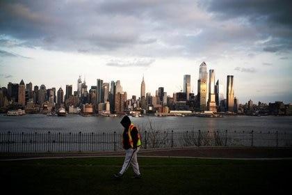 FOTO DE ARCHIVO. El edificio del Empire State y los rascacielos de Nueva York se ven mientras un hombre camina por un parque local en Weehawken, Nueva Jersey, EEUU. 22 de marzo de 2020. REUTERS/Eduardo Muñoz.