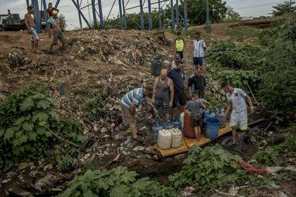 Un grupo de hombres llenaban envases de plástico con agua de un arroyo sucio, su única fuente de líquido durante los días en que no les llega el suministro. (Meridith Kohut/The New York Times)