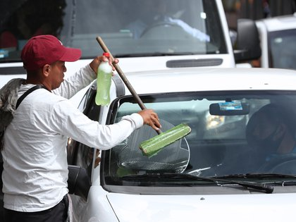 Rodrigo dejó de tener un empleo formal y pasó a vivir al día, empujado a salir a la calle armado con trapos y cloro después de fracasar también en un intento de trabajar con su padre, un fontanero falto de encargos. (Foto: EFE)