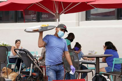FILE PHOTO: As Phase One of reopening began in Northern Virginia in May, a waiter in a face mask to protect against the coronavirus (COVID-19) carried food to diners seated outdoors at a restaurant in Alexandria, Virginia, U.S., May 29, 2020.  REUTERS/Kevin Lamarque/File Photo