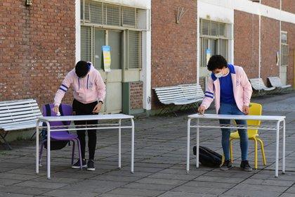 Dos alumnos del último año limpian con alcohol sus pupitres, ubicados en el patio del colegio al que asisten en Monte Castro