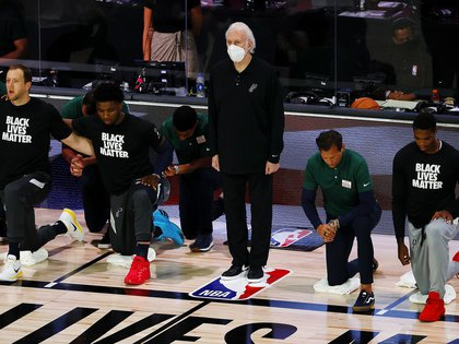Aug 13, 2020; Lake Buena Vista, Florida, USA; Gregg Popovich of the San Antonio Spurs and his team during the National Anthem prior to the start of the game against the Utah Jazz at The Field House at ESPN Wide World of Sports Complex. Mandatory Credit: Kevin C. Cox/Pool Photo-USA TODAY Sports