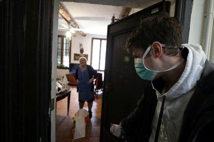 En la crisis de la pandemia las personas buscan modos de ayudarse mutuamente, como el reparto domiciliario de alimentos a las personas que no pueden salir de sus casas (Reuters/ Eric Gaillard)