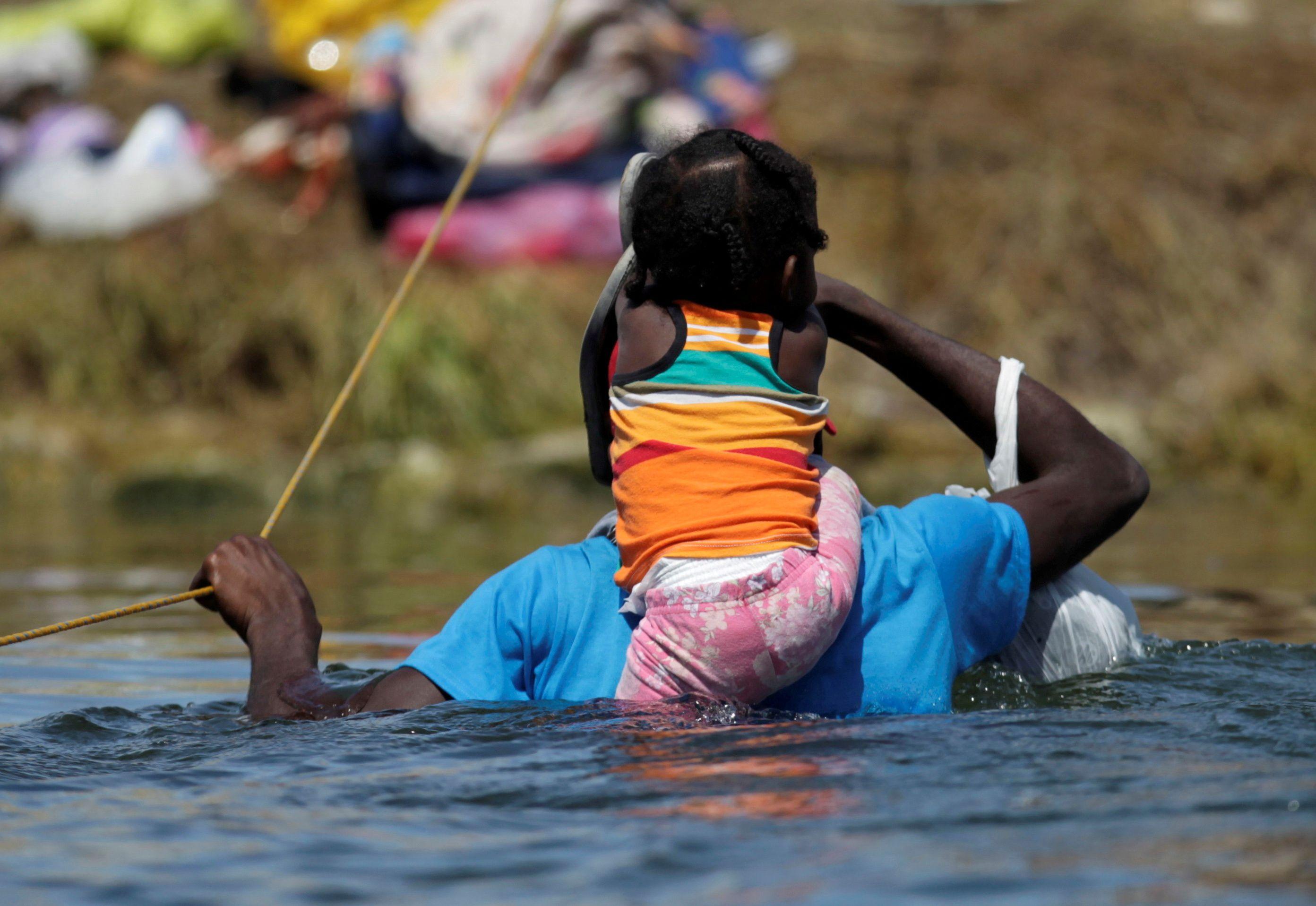 FILE PHOTO: A migrant with a child seeking refuge in the U.S. wades through the Rio Grande from Ciudad Acuna, Mexico toward Del Rio, Texas, U.S., in Ciudad Acuna, Mexico September 22, 2021. REUTERS/Daniel Becerril/File Photo