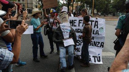 """Levantando carteles, y bajo la consigna """"Dónde está la ayuda humanitaria que nos iban a entregar"""", los manifestantes se apostaron durante horas (EFE)"""