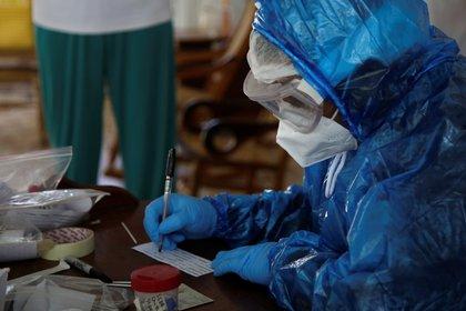 Un profesional de la salud mientras llena un formulario de prueba PCR para covid-19 durante una jornada de testeo Cartagena (Colombia). EFE/Ricardo Maldonado Rozo