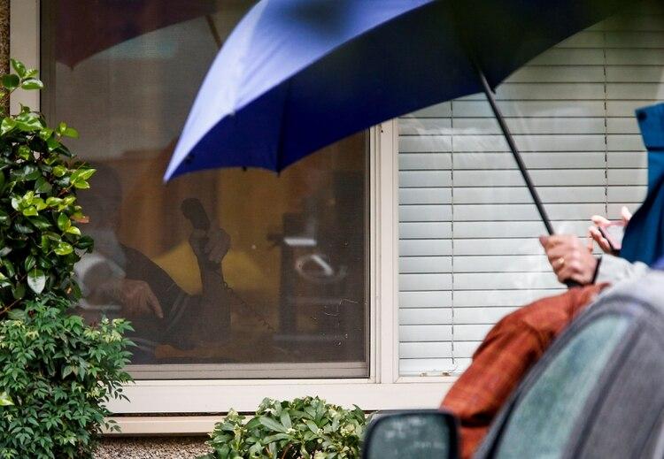 Gene Campbell, cuyo hijo Charlie dice que muestra signos de coronavirus y que se le dijo que pronto será trasladado a un hospital, le hace un gesto a Charlie a través de la ventana del Centro de Cuidado de la Vida de Kirkland el 6 de marzo de 2020 (REUTERS/Lindsey Wasson)