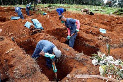 Sepultureros del cementerio de Vila Formosa, el más grande de América Latina, abren nuevas fosas este lunes para realizar más entierros dada la pandemia COVID-19, en Sao Paulo (Brasil). EFE/Sebastião Moreira