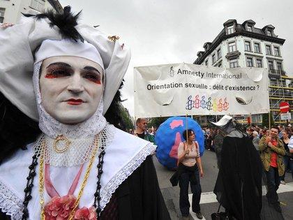 """Una multitud marchó durante un desfile del Orgullo el 17 de mayo de 2008 en el centro de Bruselas. Francia planeaba pedir a las Naciones Unidas que presionara para que la homosexualidad sea despenalizada en todo el mundo, mientras los gays y lesbianas de todo el mundo marcaban el Día Internacional contra la Homofobia, que se puso en marcha en 2005 para conmemorar el día en que en 1990 la Organización Mundial de la Salud eliminó la homosexualidad de su lista de trastornos. El letrero dice """"Orientación sexual: ¿crimen de existencia?"""""""