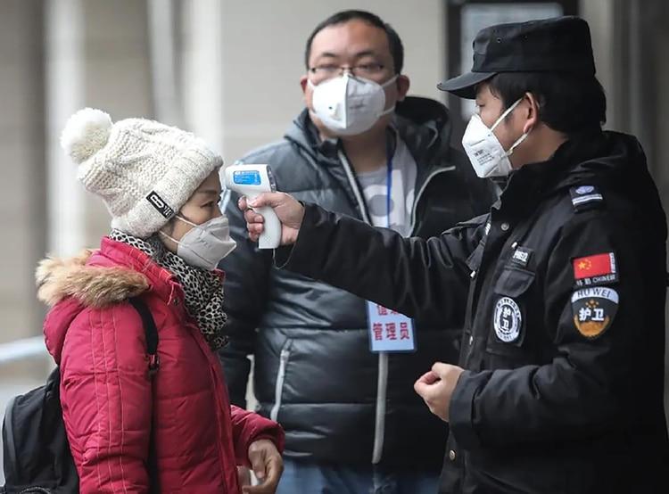 Una toma de temperatura en China. Esto detecta el síntoma, pero no evita el contagio en el período de ventana.