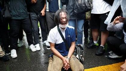 Un hombre llora mientras el coche fúnebre que lleva al difunto alcalde de Seúl, Park Won, pronto abandona la Plaza del Ayuntamiento de Seúl después de su funeral (Reuters)