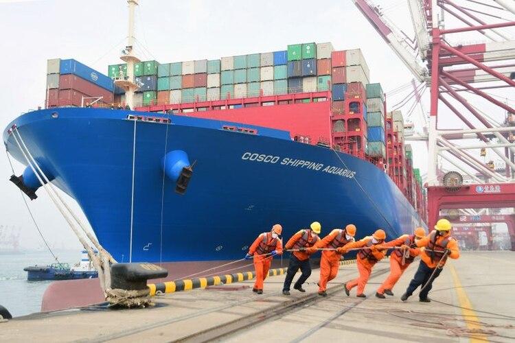 Trabajadores con mascarillas en un puerto en Qingdao, China, 11 febrero 2020. China Daily vía REUTERS